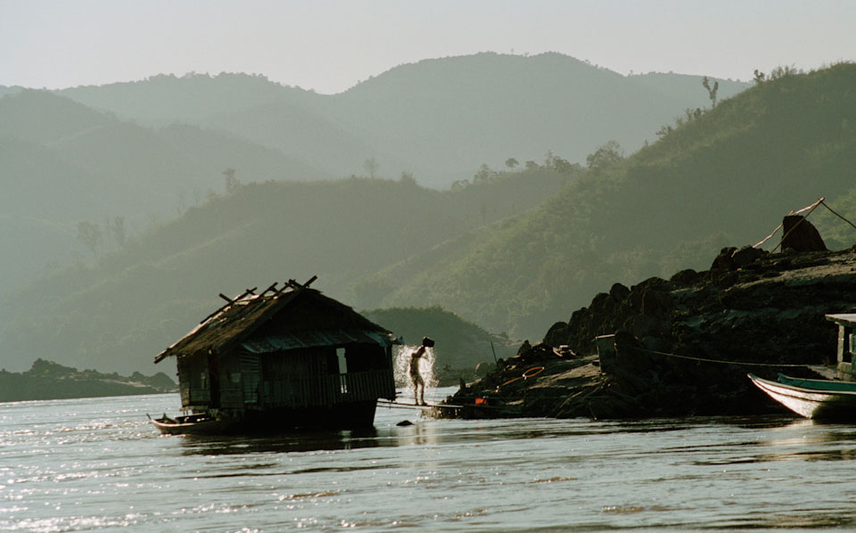 Man taking a shower on the Mekong in Laos